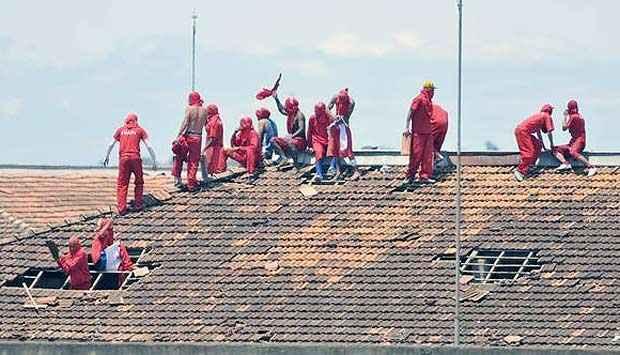 Em cima do telhado, presos tentam convencer detentos de outros pavilhões a participarem da rebelião (Juarez Rodrigues/EM/D.A.Press)