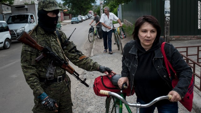 A pro-Russian fighter in Slovyansk, Ukraine, checks a woman's documents as she leaves the city on Thursday, June 12.