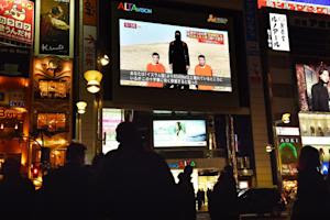 Tokyo residents look at news reports about two Japanese…