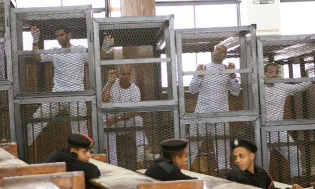 Paraded: Defendants in the cages of a Cairo courtroom. Defendants include (left to right) Student Suhaib Saeed, and Al-Jazeera journalists Peter Greste, Mohamed Fahmy and Baher Modhamed