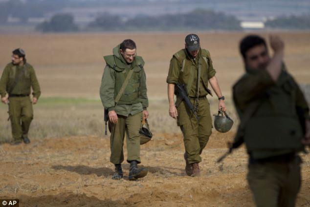 Ready: Israeli reserve soldiers walk near the Israel Gaza Border in southern Israel