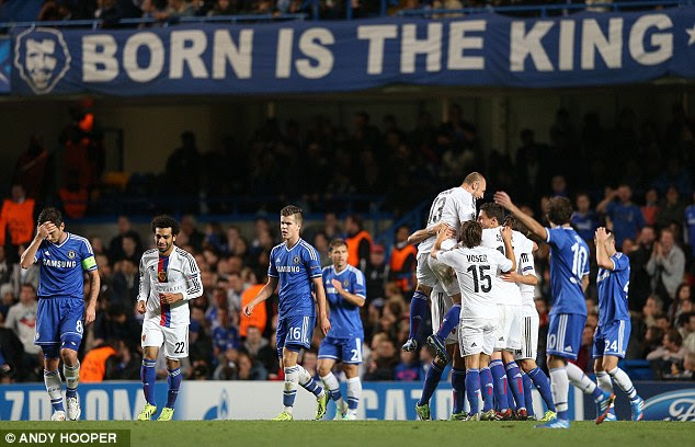 Head in hands: Frank Lampard (left) looks stunned as Basle celebrate their shock victory at Stamford Bridge
