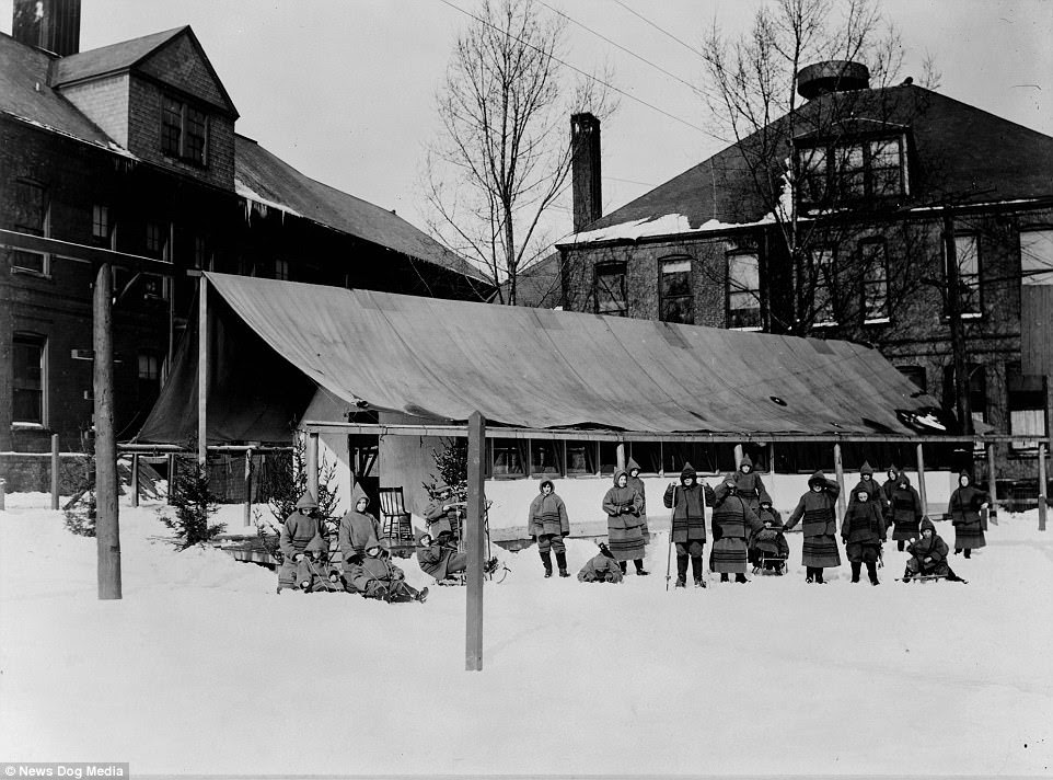 These black and white images show the open air schools of the early twentieth century - where children braved freezing temperatures in an attempt to combat the widespread rise of tuberculosis. Children are pictured with sleds outside of their open-air school in Rochester, New York,  circa 1910s