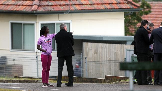 A woman, believed to be a family member, talks to police outside the house. Picture: Liam