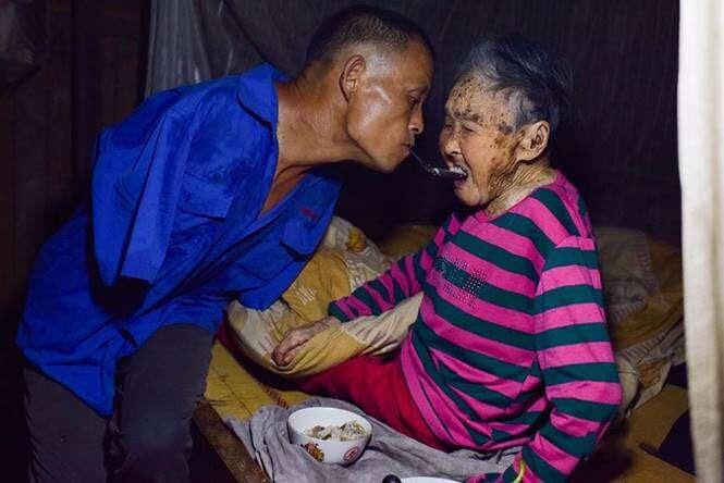 Filho sem braços alimentando mãe