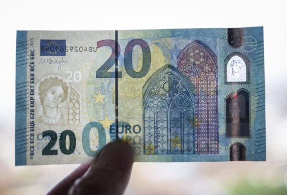 Un miembro del banco federal alemán muestra un nuevo billete de 20 euros a trasluz, con lo que se ven las nuevas marcas de agua, la ventana de seguridad y el diseño
