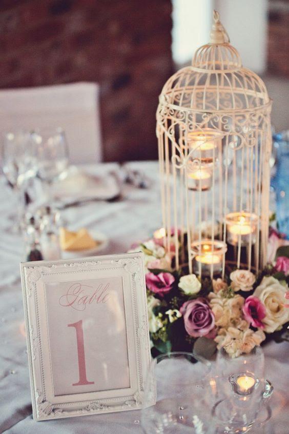 ein weißer Käfig mit Teelichter und Fett Blüten umgeben, die den Käfig