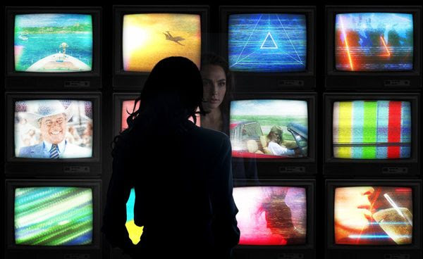 A promo pic of Diana Prince staring at a group of TV sets in WONDER WOMAN 1984.