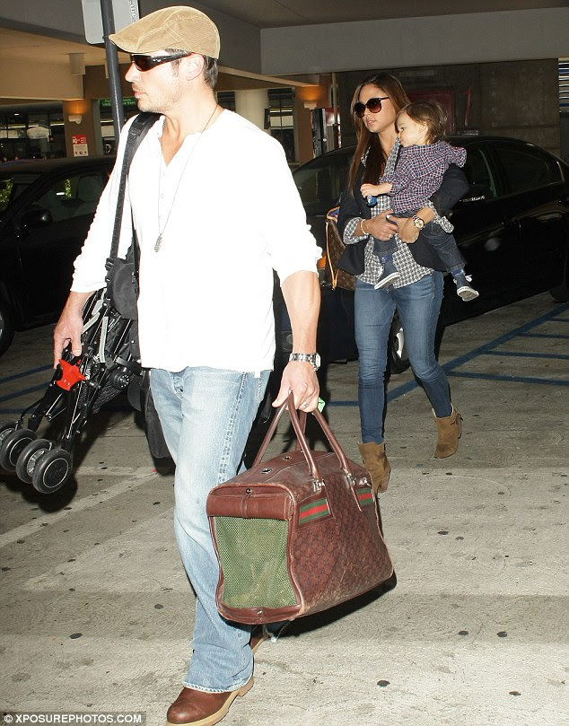 Quite the load: The star carried his son's stroller and a large travel bag as his partner hip carried their sleepy child