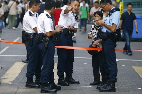 Police officers give instructions to a commuter in an area occupied by pro-democracy protesters at Mongkok shopping district in Hong Kong October 29, 2014. REUTERS-Damir Sagolj