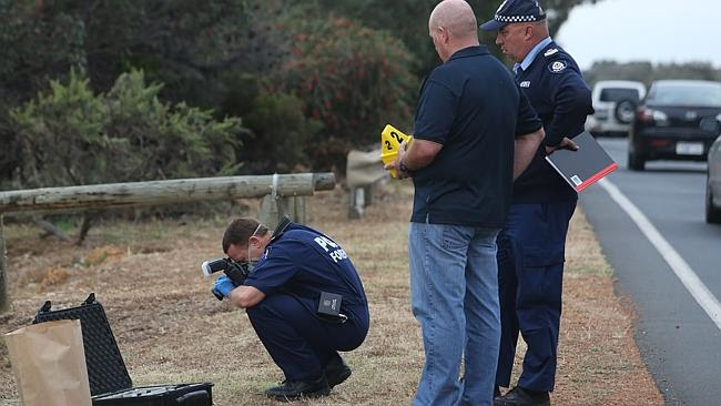 A police forensic officer photographs an item of interest at Australind. Picutre: Bohdan Warchomij