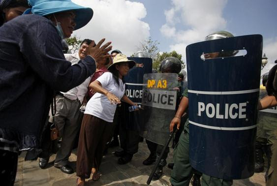 Protesters are blocked by police officers during a demonstration in central Phnom Penh March 31, 2014. REUTERS-Samrang Pring