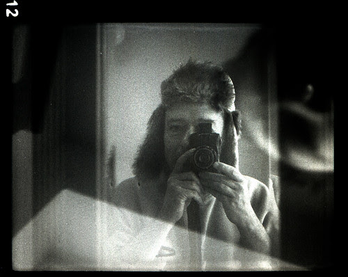 reflected self-portrait with Zeiss Kolibri camera and winter hat by pho-Tony