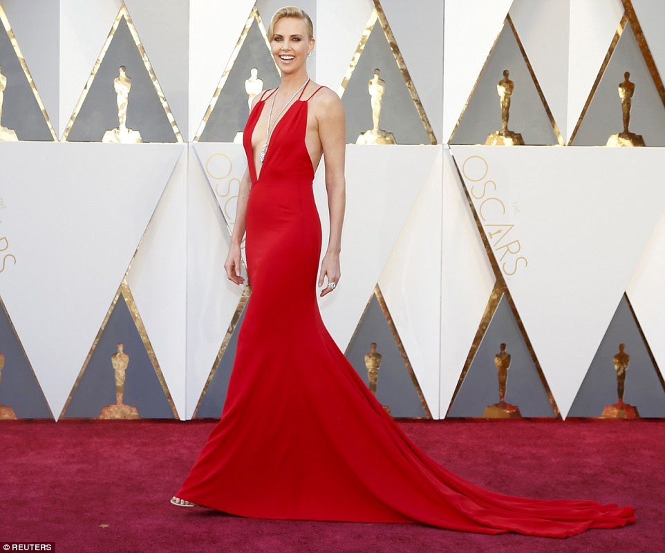Saucy in scarlet: Charlize Theron was all about the sex appeal in a very low-cut and slinky red gown by Christian Dior