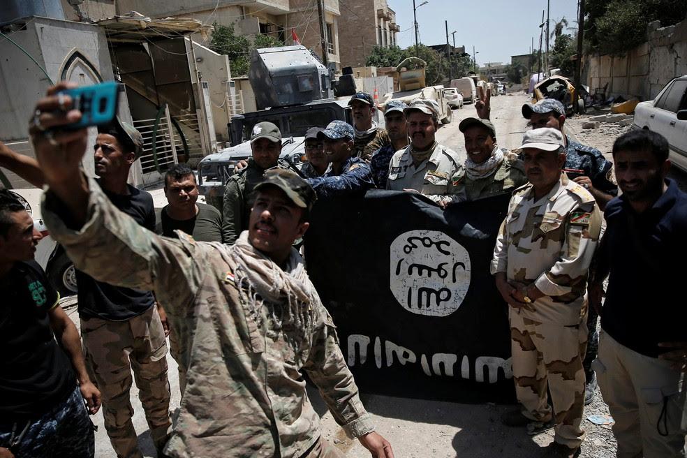 Membros do Exército iraquiano tiram selfie com uma bandeira do Estado Islâmico tomada após conflito com jihadistas em Mossul (Foto: Alkis Konstantinidis/Reuters)