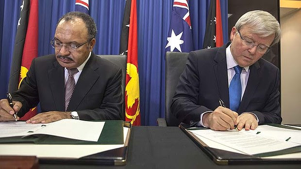 Papua New Guinea's Prime Minister Peter O'Neill and Australian Prime Minister Kevin Rudd sign an agreement over asylum seekers on 19th July 2013.