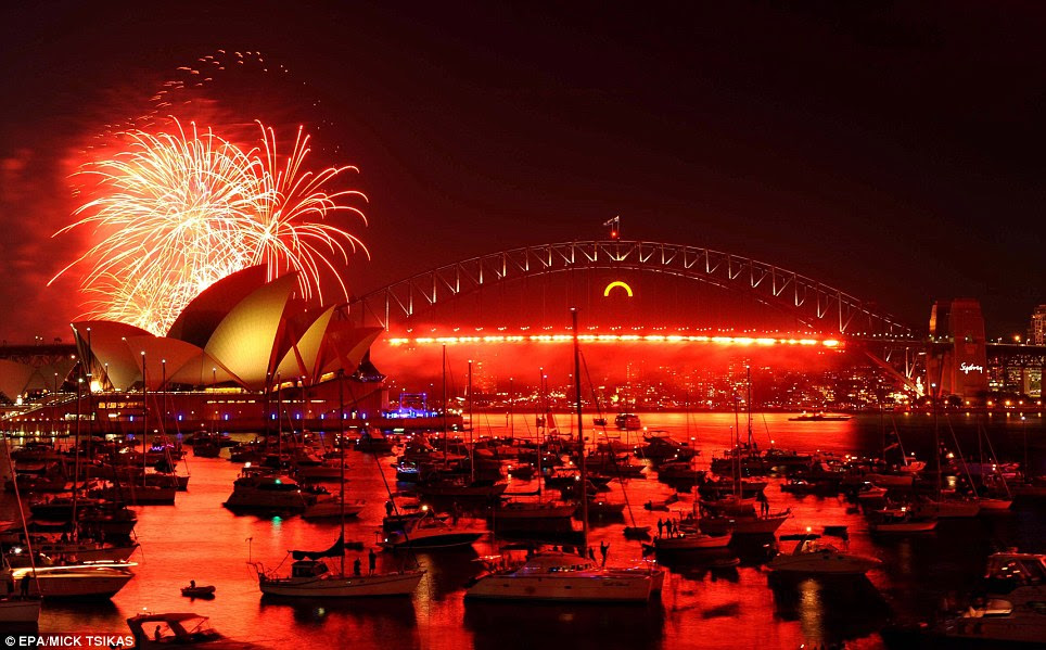 AUSTRALIA: A red hue lights up the sky over the Sydney Opera House. More than a million people gathered to watch and then celebrate 2012
