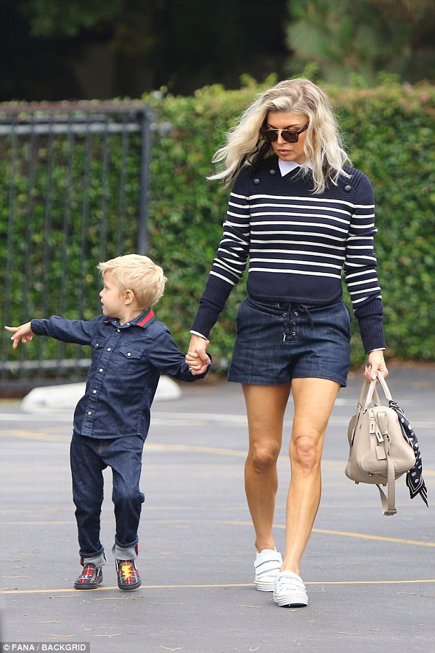 On the go: Showing off her legs in a pair of midnight blue shorts, Fergie had completed the look with white sneakers, accessorizing with double-bridge shades and a tan purse