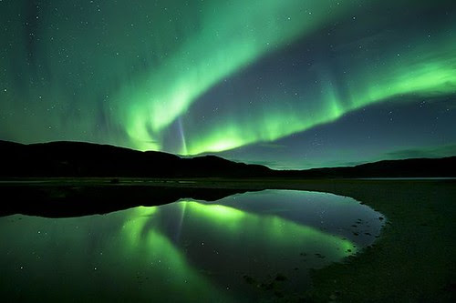 Aurora+borealis,+the+spectacular+Northern+Lights+turn+the+sky+green+at+Ifjord+in+Finnmark,+Norway