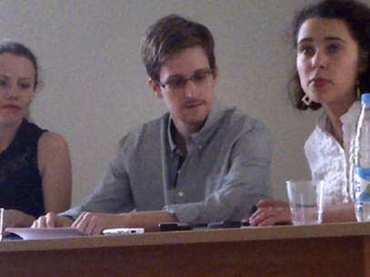 Foto aportada por Human Rights Watch del confidente Edward Snowden, centro, en una conferencia de prensa en el aeropuerto Sheremetyevo de Moscú con Sarah Harrison, de WikiLeaks (Izq.)el 12 de julio del 2013. Foto: AP