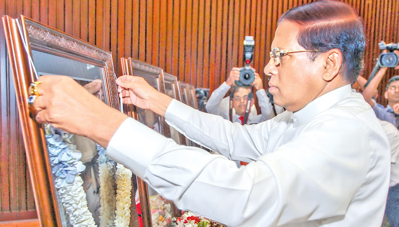The Sri Lanka Freedom Party honoured trade union leaders at a ceremony held at the BMICH under the patronage of President Maithripala Sirisena yesterday. Picture shows the President garlanding the portraits of former SLFP Trade Union leaders on the occasion. Picture by Sudath Silva