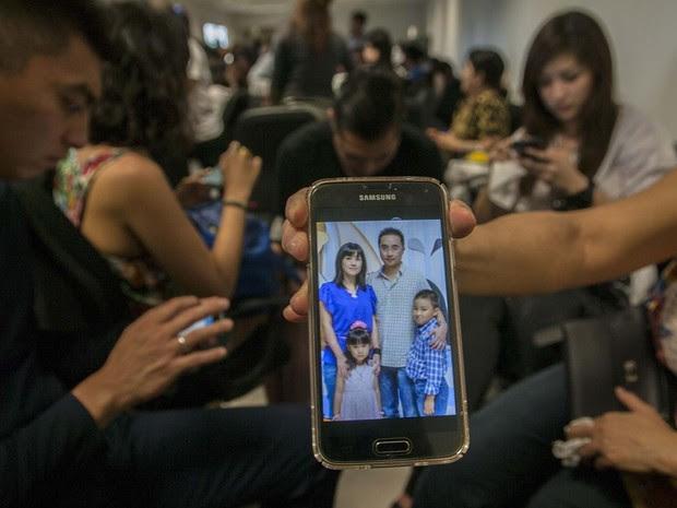 Parente no aeroporto de Surabaya mostra foto de família que diz que estava viajando no avião da AirAsia que desapareceu neste domingo (28) (Foto: AFP Photo / Juni )