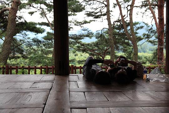식영정 마루에 누우면 여름이 느껴지지않는다. 한 커플이 마루에 누워있다.