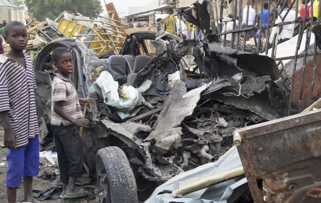 Image: Two boys stand near charred chassis of vehicle after bomb attack near busy market area in Ajilari-Gomari near city's airport, in Maiduguri