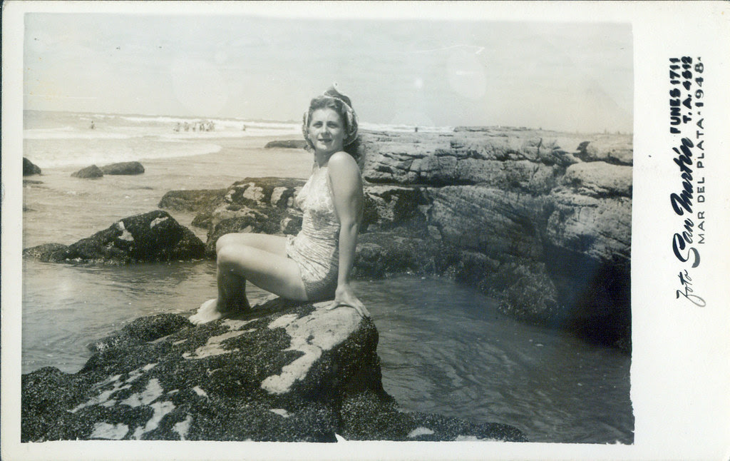 By the sea - One girl on rocks in a one-piece suit