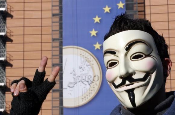 Un joven con una máscara de Anonymous frente a la Comisión Europea, en Bruselas (Bélgica), con la moneda de euro en su fachada. Foto: Reuters.