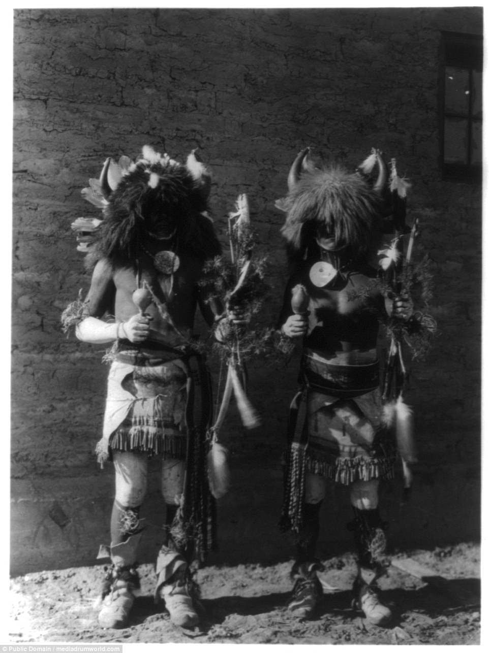 Two Native American men in costumes wearing horns of buffaloes pictured in 1907
