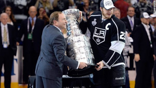 Los Angeles Kings team captain Dustin Brown poses with NHL Commissioner Gary Bettman after the Kings defeated the New York Rangers, 3-2, in Game 5 of the Stanley Cup Finals at STAPLES Center...on June 13, 2014.
