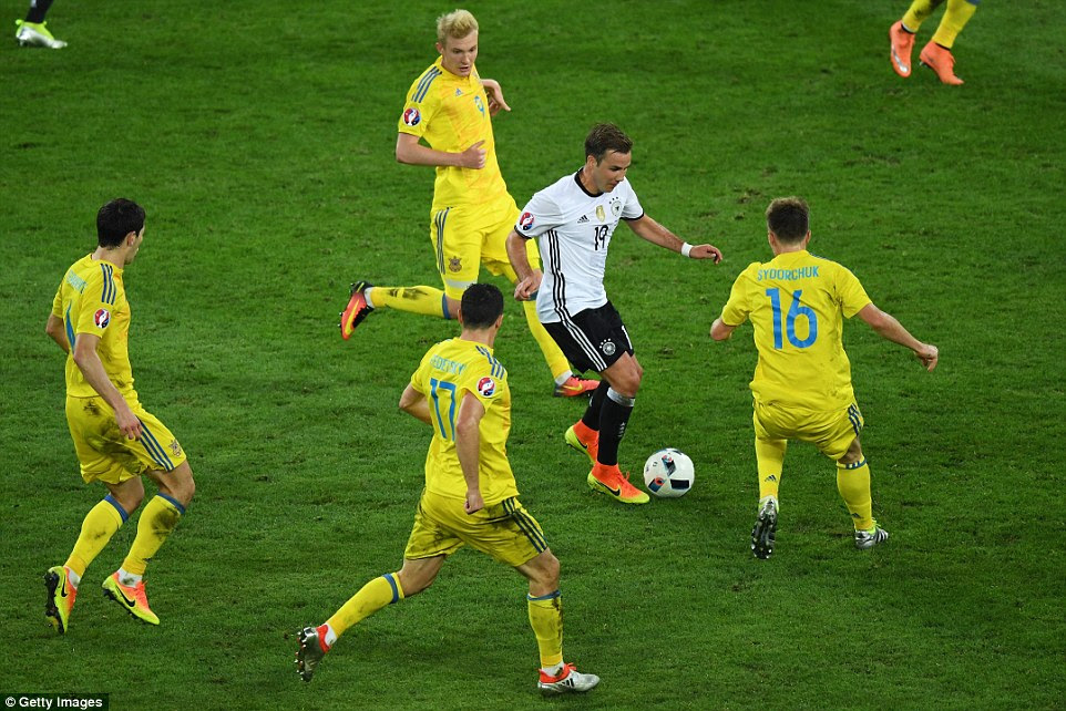 Bayern Munich's Gotze (No 19) tries to escape the challenges of several Ukraine players as he goes on a mazy dribble