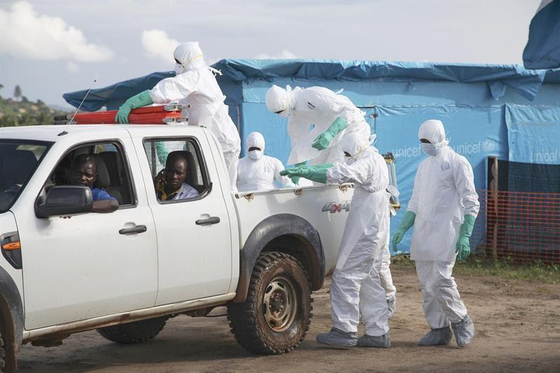 Funcionários de um centro médico usam roupas protetoras para enterrar uma paciente que morreu de ebola (Foto: efe)