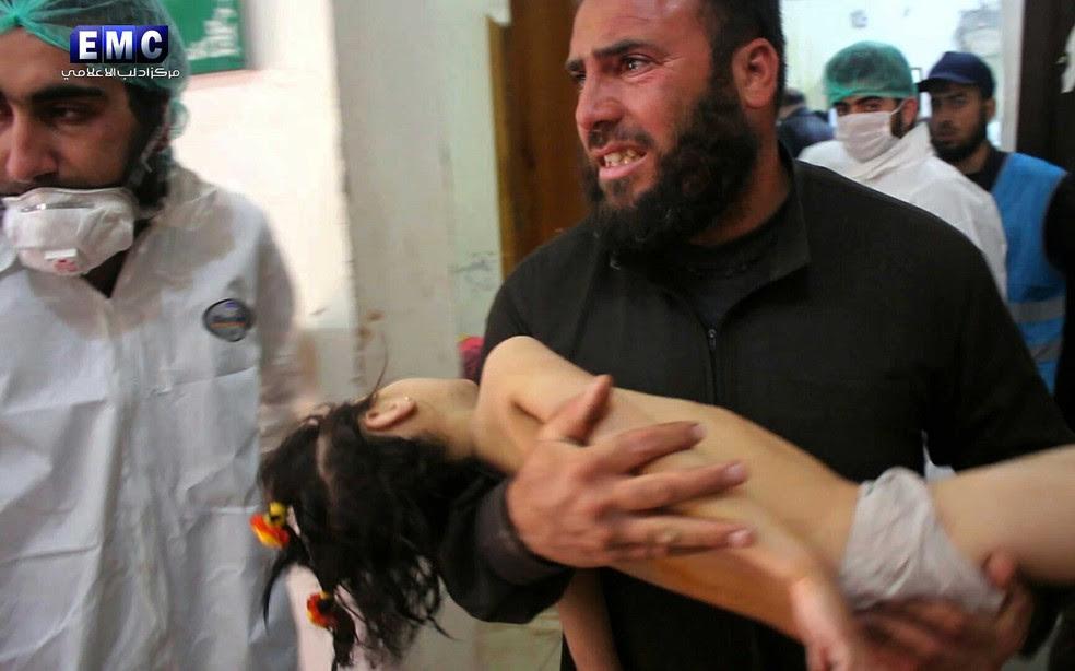 Homem socorre criança após suposto ataque químico em Idlib, no norte da Síria, nesta terça-feira (4)  (Foto: Edlib Media Center, via AP)