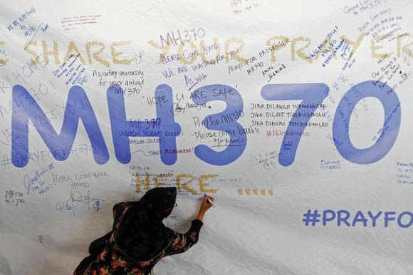 A woman writes a message of support and hope for the passengers of the missing Malaysia Airlines MH370 on a banner at Kuala Lumpur International Airport March 12, 2014. REUTERS/Damir Sagolj