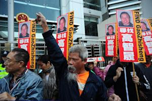 Protesters carrying placards featuring the photograph…