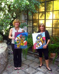 lynn and laurie with paintings they bought from a local artist