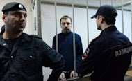 Mikhail Kosenko, an activist accused of violence at a rally on the eve of President Vladimir Putin's inauguration, stands in a defendant's cage in a court in Moscow on October 8, 2013