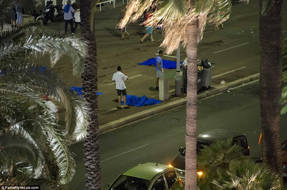 Desolado: Dois homens estão ao lado de corpos, com um sobre um telefone móvel, como muitas famílias perderam entes queridos no ataque terror na noite passada