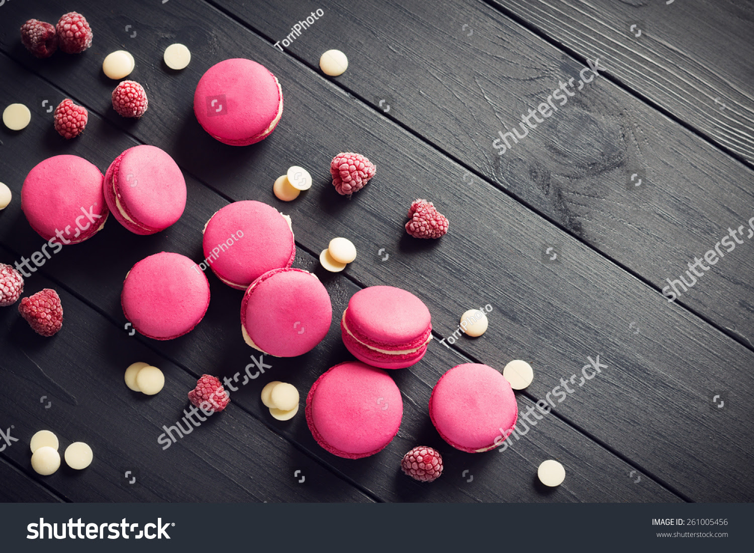 http://www.shutterstock.com/pic-261005456/stock-photo-pink-macaroons-with-raspberries-and-white-chocolate-drops-on-black-wooden-background.html