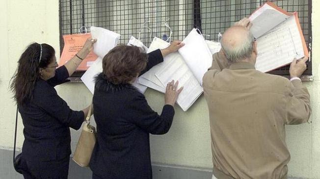 Unos votantes consultan los censos electorales.