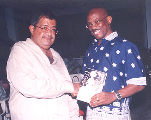 "Anthony Kissoon gives a copy of his first collection of ""Tales of the Spirits"" to Mayor Hamilton Green"