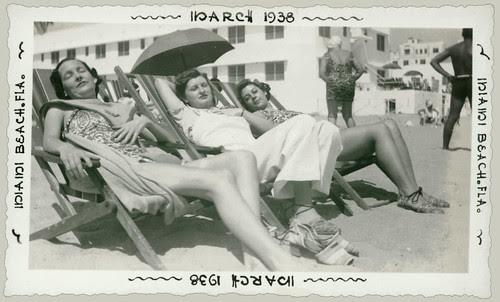 Three women asleep on the beach