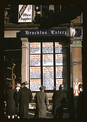 Men and a woman reading headlines posted in st...