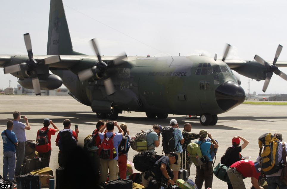 Local and foreign medical teams prepare to board a Philippines air force C-130 transport plane in Manila