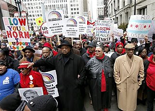 Karen Lewis, center, president of the Chicago Teachers Union is joined by the Rev. Jesse Jackson, left, and U.S. Rep. Bobby Rush, right, during a demonstration and march over the a plan to close 54 Chicago Public Schools through Chicago's downtown. by Pan-African News Wire File Photos