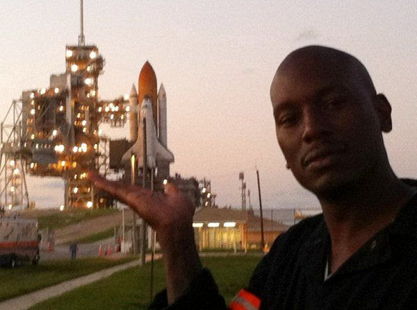 Actor/rapper Tyrese Gibson poses in front of space shuttle Discovery at Launch Complex 39A.