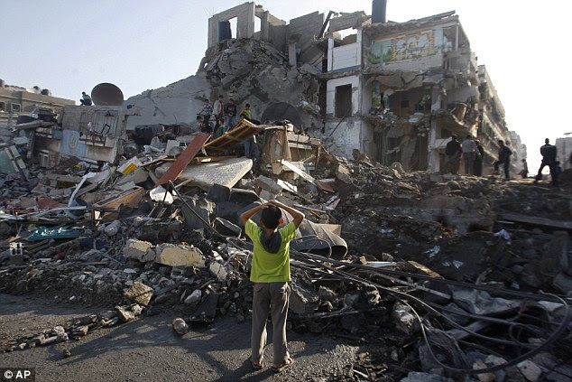 Devastation: Palestinian children stand in the rubble left after an Israeli strike on a house in Gaza City on Tuesday