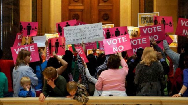 Demonstrators against gay marriage bill wave their signs outside the Minnesota House chamber before lawmakers arrive to take up the legislation at the State Capitol, Thursday, May 9, 2013.